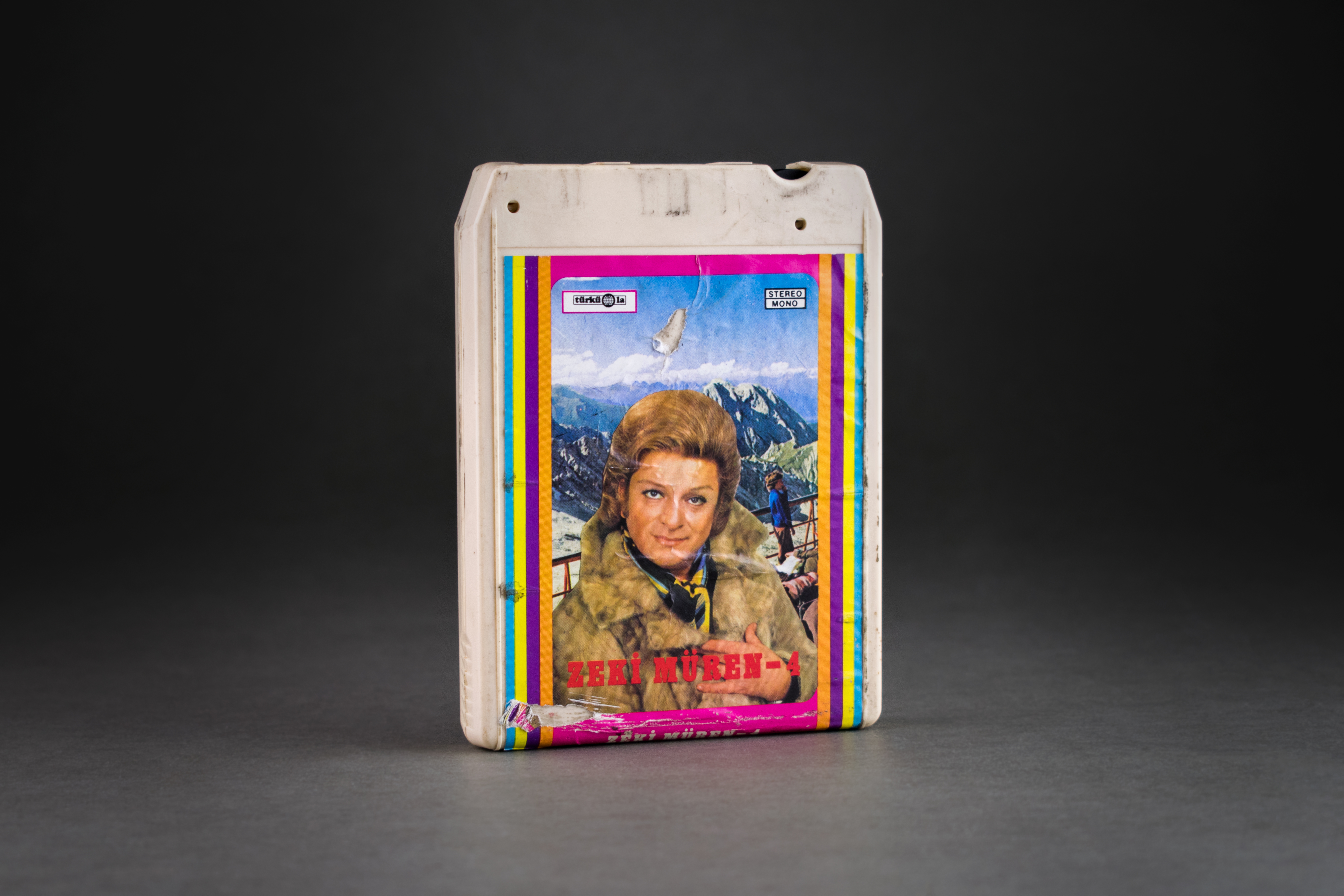 8-track cassette by Zeki Müren, Türküola, 1970. Türküola was the first record company to produce Turkish-language music in Germany. It was founded by Yılmaz Asöcal in Cologne in the 1960s. In addition to LPs, cassettes and later also CDs from well-known Turkish-speaking artists such as Barış Manço, İbrahim Tatlıses or Zeki Müren, from the 1960s, Türküola also contracted numerous migrant workers who had only started a musical career in Germany. This group also included the two best-selling artists from the record label, Metin Türköz and Yüksel Özkasap, who also gained fame in Turkey. In the 1980s, Türküola produced the albums of the well-known musician Cem Karaca. DOMiD Archive, Cologne, BT 0612,0008